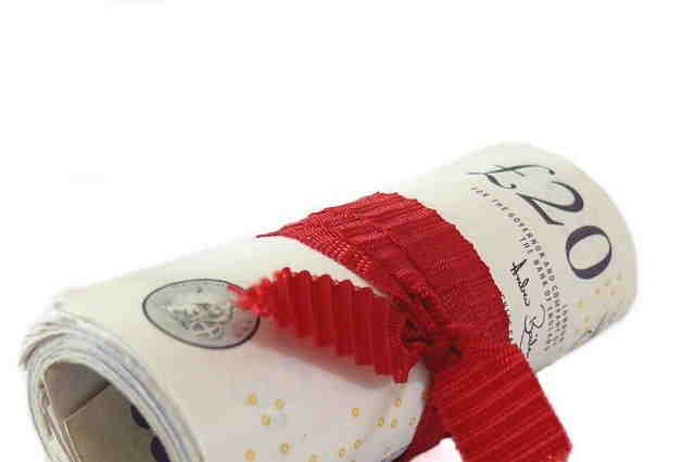 rolled up bank notes tied with a red ribbon